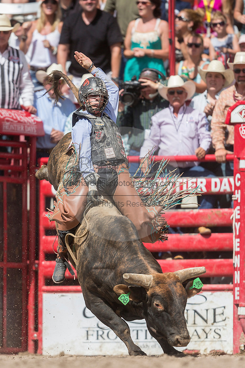 Bull rider Sage Kimzey of Strong City, Oklahoma emerges from the chute riding Lit Em Up at the Cheyenne Frontier Days rodeo at Frontier Park Arena July 24, 2015 in Cheyenne, Wyoming. Frontier Days celebrates the cowboy traditions of the west with a rodeo, parade and fair.