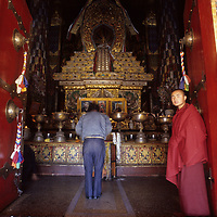 CHINA, TIBET. Tibetan Buddhist monk by door into richly ornamented Tshomchen, the Main Assembly Hall at Palkhor Monastery in Gyantse.