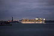 The Princess Line's Caribbean Princess passes the Statue of Liberty in the dusk with still dark Elizabeth New Jersey in the background on its way to the Caribbean. It's prior cruise was sailed around Sandy, and put in to New York late.