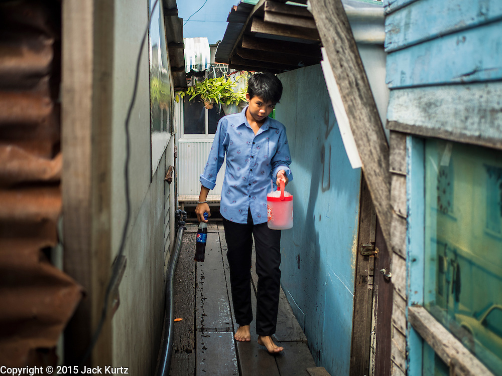 22 JULY 2015 - BANGKOK, THAILAND:    A woman walks between houses in a community along the Chao Phraya River south of Krung Thon Bridge. This is one of the first parts of the riverbank that is scheduled to be redeveloped. The communities along the river don't know what's going to happen when the redevelopment starts. The Chao Phraya promenade is development project of parks, walkways and recreational areas on the Chao Phraya River between Pin Klao and Phra Nang Klao Bridges. The 14 kilometer long promenade will cost approximately 14 billion Baht (407 million US Dollars). The project involves the forced eviction of more than 200 communities of people who live along the river, a dozen riverfront  temples, several schools, and privately-owned piers on both sides of the Chao Phraya River. Construction is scheduled on the project is scheduled to start in early 2016. There has been very little public input on the planned redevelopment.           PHOTO BY JACK KURTZ