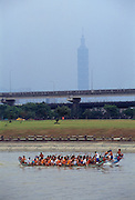 Dragon boats, a traditional Chinese form of water transportation, prepare for races on the Jilong River.  Taipei 101 looms in the background.