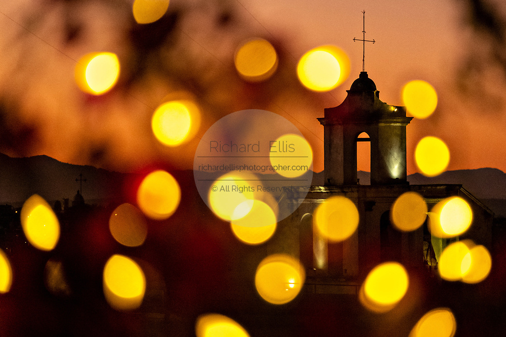 Colorful sunset fairy lights decorate the view of the bell tower on the Old Convent of San Antonio in the historic city center of San Miguel de Allende, Mexico.
