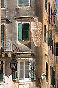 Traditional lanterns and window shutters in street scene in Old Town of Kerkyra, Corfu Town, Greece