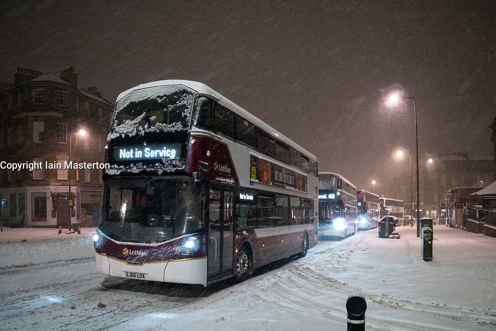 Edinburgh, Scotland, UK. 10 Feb 2021. Big freeze continues in the UK with heavy overnight and morning snow bringing traffic to a standstill on many roads in the city centre. Pic; Lothian buses struggle on Leith Walk at 6am. Iain Masterton/Alamy Live news