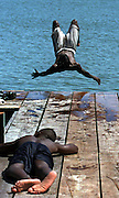 .Sammie Harris, 15, center, does a flip from the dock into Lake Nokomis in Minneapolis on a muggy  afternoon as he joined friend James Davis, 13, left,  for a swim to escape from the heat and hmidity of another 100 degree July day.....