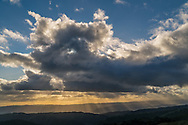 Crepuscular Rays (sunbeams) at sunset behind stratocumulus clouds over Henry Coe State Park, Santa Clara County, California