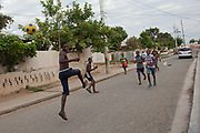 Young men playing football in the street. Trenchtown, Kingston, Jamaica.