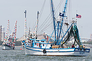 Decorated shrimp boats parade down the Cooper River during the annual Blessing of the Fleet signifying the start of the commercial shrimping season April 30, 2017 in Charleston, South Carolina. Coastal shrimping is part of the low country heritage but has been declining rapidly with rising costs and increased foreign competition.
