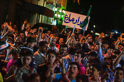 People holding banners, placards, Syrian revolutionary flags as well as saluting with two fingers demanding respect to their civil, human as well as political rights and liberties are gathered outside the media and cultural centre in Marea on Friday night, May 25, 2012 - during an anti-government demonstration. (Photo by Vudi Xhymshiti)