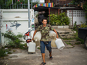 05 OCTOBER 2015 - BANGKOK, THAILAND:  A man being evicted leaves the Wat Kalayanamit neighborhood with empty water bottles. Fifty-four homes around Wat Kalayanamit, a historic Buddhist temple on the Chao Phraya River in the Thonburi section of Bangkok, are being razed and the residents evicted to make way for new development at the temple. The abbot of the temple said he was evicting the residents, who have lived on the temple grounds for generations, because their homes are unsafe and because he wants to improve the temple grounds. The evictions are a part of a Bangkok trend, especially along the Chao Phraya River and BTS light rail lines. Low income people are being evicted from their long time homes to make way for urban renewal.        PHOTO BY JACK KURTZ