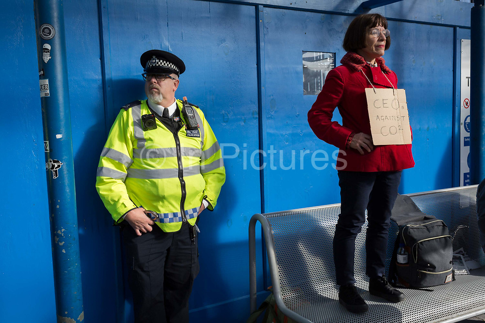 As environmental activists protest about Climate Change, police officers secure the outside the terminal building during the occupation of City Airport Londons Business Travel hub in east London, the fourth day of a two-week prolonged worldwide protest by members of Extinction Rebellion, on 10th October 2019, in London, England.