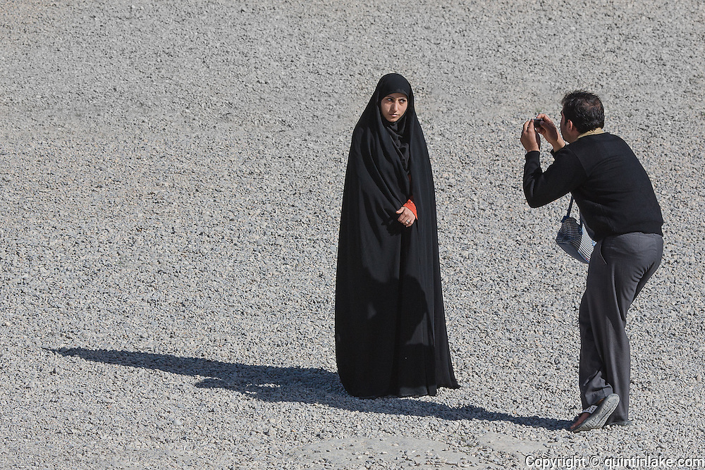 A lady wearing a chador posing for a photo at Persepolis. Persepolis was the ceremonial capital of the Persian Empire (550-330 BC) during the Achaemenid dynasty. Persepolis, Iran, 2008