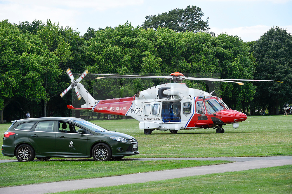 © Licensed to London News Pictures. 03/07/2019. LONDON, UK.  A Coastguard Rescue helicopter waits to take off from Regent's Park after collecting equipment from a Children's Acute Transport Service (CATS) ambulance on behalf of nearby Great Ormond Street Hospital.  The helicopter will make the journey to collect a sick child who will be brought back for treatment at Great Ormond Street as travel by road would take too long.  Photo credit: Stephen Chung/LNP