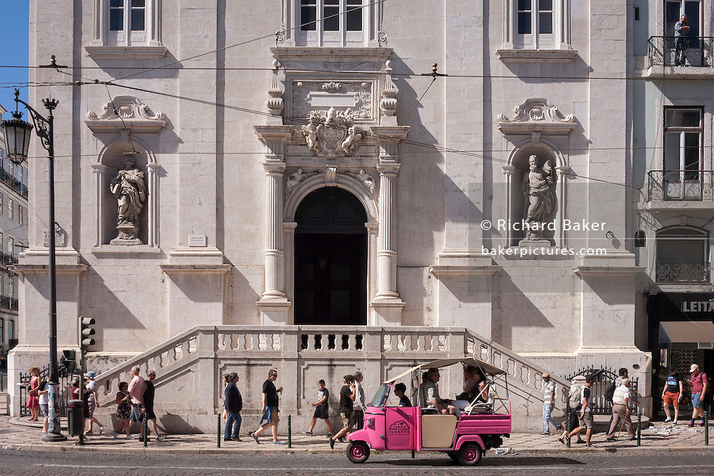 """A pink Tuk Tuk has stopped at a red light outside Igreja de Nossa Senhora do Loreto (church) during a city sightseeing tour through Praca Luis Camoes, on 11th July 2016, in Lisbon, Portugal. The company operating these vehicles is Turma das Ilusoes """"Organization of touristic and cultural activities, thematic tours, with or without advertising."""" The Church of Loreto, is next to Largo do Chiado at the corner with Rua da Misericordia. With the Lisbon earthquake of 1755 the church suffered extensive damage and was rebuilt in 1785. (Photo by Richard Baker / In Pictures via Getty Images)"""