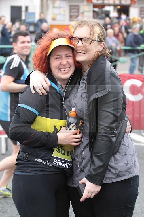 © Licensed to London News Pictures. 06/04/2014. Brighton, UK. The couple hug after the proposal was accepted. A marriage proposal took place during the Brighton Marathon today 6th April. Lucy Beasley (right) proposed to Chantelle Dunstan who was running the marathon for Guidedogs.org. Photo credit : Hugo Michiels/LNP