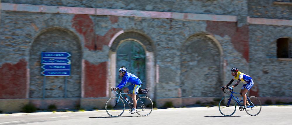 Cyclists pass signpost on The Stelvio Pass, Passo dello Stelvio, Stilfser Joch, in Northern Italy