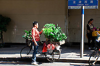 Local plant vendor sits with his good on his bicycle in Long Jin Xi Lu, Guangzhou.