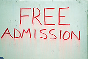 Free Admission sign in red paint on white board