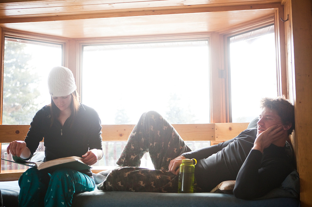 A young man reads a book at Francie's Hut, a backcountry cabin in Arapaho National Forest, Colorado.