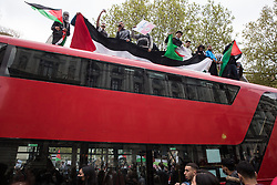 London, UK. 11th May, 2021. Pro-Palestinian demonstrators climb on top of a bus outside Downing Street as thousands of people attend an emergency protest in solidarity with the Palestinian people organised by Palestine Solidarity Campaign, Friends of Al Aqsa, Stop The War Coalition and Palestinian Forum in Britain. The rally took place in protest against Israeli air raids on Gaza, the deployment of Israeli forces against worshippers at the Al-Aqsa mosque during Ramadan and attempts to forcibly displace Palestinian families from the Sheikh Jarrah neighbourhood of East Jerusalem.