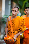 """11 MARCH 2013 - LUANG PRABANG, LAOS:  A Buddhist monk walks through the streets of Luang Prabang during the tak bat. The """"Tak Bat"""" is a daily ritual in most of Laos (and other Theravada Buddhist countries like Thailand and Cambodia). Monks leave their temples at dawn and walk silently through the streets and people put rice and other foodstuffs into their alms bowls. Luang Prabang, in northern Laos, is particularly well known for the morning """"tak bat"""" because of the large number temples and monks in the city. Most mornings hundreds of monks go out to collect alms from people.   PHOTO BY JACK KURTZ"""