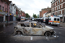 © Licensed to London News Pictures. 07/08/2011. Tottenham, UK. A gutted and burned out police car lies in the middle of Tottenham High Street. Mass rioting and vandalism broke out along Tottenham High Street and many building were set alight. Photo credit : Joel Goodman/LNP