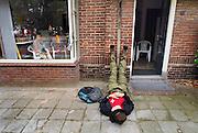 Nederland, Nijmegen, 17-7-2008Vierdaagse, de dag van Groesbeek. Traditioneel de zwaarste vanwege de zevenheuvelenweg die een vijftal heuvels heeft tussen Groesbeek en Berg en Dal. Hier de doorkomst in Berg en Dal. Een loper uit Zwitserland laat zijn benen rusten tegen de gevel van een huis. De bewoonster kijkt intussen naar de wandeltocht.Foto: Flip Franssen/Hollandse Hoogte