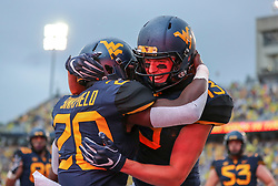 Sep 8, 2018; Morgantown, WV, USA; West Virginia Mountaineers wide receiver David Sills V (13) celebrates with West Virginia Mountaineers running back Alec Sinkfield (20) after he ran for a touchdown during the first quarter against the Youngstown State Penguins at Mountaineer Field at Milan Puskar Stadium. Mandatory Credit: Ben Queen-USA TODAY Sports