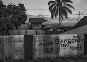 Saint-Georges de l'Oyapock, Guyane, 2015.<br /> <br /> La commune de Saint-Georges s'étend sur 2320 km2 et doit son origine à la création d'un bagne dont il ne reste plus de trace. Ce camp construit en 1853 pour contenir la présence brésilienne est une des pires expériences de la déportation guyanaise. Du fait des maladies tropicales, c'est un des bagnes où la mortalité est la plus forte. Face à l'hécatombe, on y envoie les condamnés d'origine africaine jugés plus résistants. Bien sur le taux de mortalité ne faiblit pas et le camp est fermé en 1863. Après la découverte d'or en 1885, Saint-Georges se repeuple et devient un camp de base pour l'orpaillage. La commune de Saint-Georges de l'Oyapock est officiellement créée en 1946.<br /> <br /> Au début des années 2000, Saint-Georges est un village créole totalement enclavé, tourné vers le Brésil, accessible par une piste commandée par l'État à la légion et desservie par des taxis clandestins locaux, c'est à dire brésiliens. Une liaison aérienne irrégulière permet d'effectuer les déplacements vers Cayenne, la capitale. L'ouverture de la Route Nationale 2 permet de rallier le littoral en 3 heures depuis 2003, l'aérodrome n'est plus utilisé que par les hélicoptères desservant le centre de santé. Jusque-là très isolée, Saint-Georges a développé une stratégie sociale, économique et culturelle structurée par le fleuve, véritable communauté de vie pour ses riverains qui parlent à la fois brésilien et français, créole et amérindien.<br /> <br /> La bourgade ouvre l'oeil deux fois par jour : quand les écoliers sortent à 13h30 et quand les deux bars restaurants se réveillent à 18h. Entre temps, rien. Ou presque. Le 7 de chaque mois, au moment du versement des prestations sociales, St Georges s'anime. Pendant 48h, les commerçants sortent leurs ardoises, le distributeur d'argent s'essouffle et les cadavres de Heineken s'accumulent. Sur la place, les buveurs de rhum de l'administration publique pestent contre les buveurs de bière de