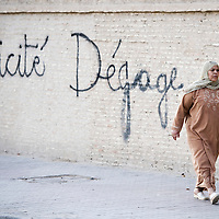 USE ARROWS ← → on your keyboard to navigate this slide-show<br /> <br /> Kairouan, Tunisia, 27 October 2011<br /> A Tunisian woman walks in front of a graffiti against secularism.<br /> Photo: Ezequiel Scagnetti