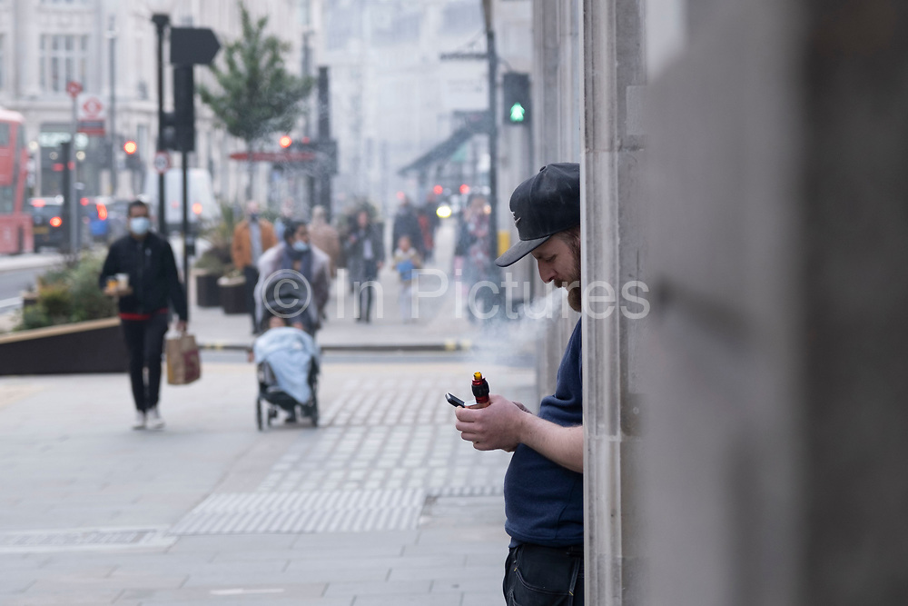 Man taking a break vaping while staring at his smart phone on Regent Street on 3rd March 2021 in London, England, United Kingdom. Vaping is often seen as a safe or safer alternative to smoking. It is also relatively new to the market, only hitting the mainstream over the past decade or so.