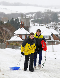 © Licensed to London News Pictures. 11/12/2017. Amersham, UK. Carl and Elliot pull their sledges up a hillside in the town of Amersham Station in Buckinghamshire. Further snowfall has hit parts of the south east of England causing travel disruption. Photo credit: Tom Nicholson/LNP