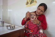 A Nepalese baby is fed nutritious food by her mother in the dining room at the Friends of Needy Children Nutritional Rehabilitation Centre, Kathmandu, Nepal.  The child is an inpatient in the centre and receiving intensive treatment for malnutrition. The centre has recently been built to provide healthcare to malnourished children and education to mothers about nutrition and childcare.