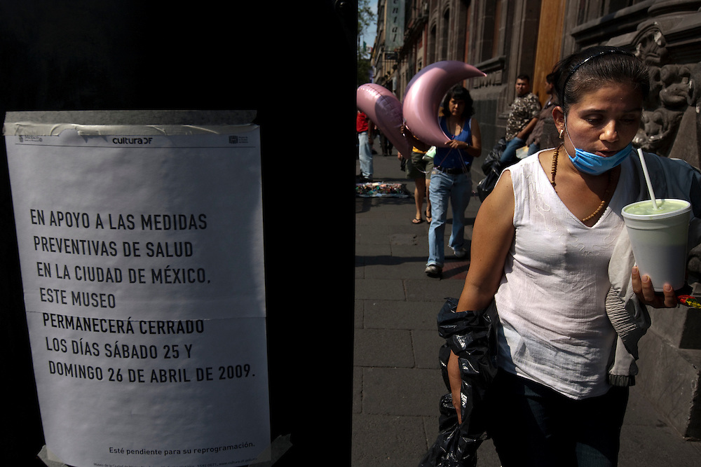 24 April 2009, Mexico City, Mexico---  A woman wearing a surgical mask walks past a sign announcing the closure of the Mexico City Museum . All museums, public buildings, and events were indefintily closed on Friday as the Mexican government attempts to halt the growth of a deadly strain of Swine Flu.   The  --- Image by © Trevor Snapp