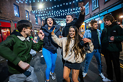© Licensed to London News Pictures. 12/04/2021. Manchester, UK. People dance to music played through a portable stereo in the Northern Quarter of Manchester City Centre on a night out , as government restrictions to control the spread of Coronavirus are eased across the UK. Pubs, restaurants, hairdressers, gyms and non essential retailers are now permitted to serve customers within restrictions. Photo credit: Joel Goodman/LNP