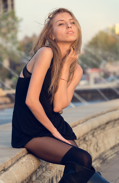 Sexy attractive woman in a short black dress and long boots posing sitting on a wall outdoors with her face raised to the evening sunlight