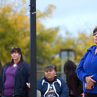 City Councilor Fran Palochak listens to guest speaker Char James at the start of the Battered Families Services Vigil in downtown Gallup Sunday. Palochak played guitar and sang during the vigil as well.