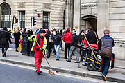 A British street cleaner sweeps the road to clean and collected refuse amongst many commuters at the busy Bank junction in central London, United Kingdom.  The street cleaning service is provided by the City of London Corporation which is the municipal governing body.