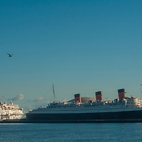 Both a modern Carnival cruise ship and the venerable Queen Mary (now a floating hotel) anchor in Long Beach Harbor, California.
