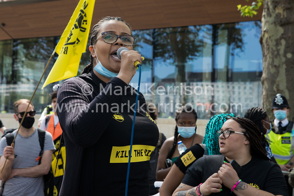 London, UK. 29th May, 2021. A United for Black Lives activist addresses fellow civil rights and other activists outside New Scotland Yard during a Kill The Bill National Day of Action in protest against the Police, Crime, Sentencing and Courts (PCSC) Bill 2021. The PCSC Bill would grant the police a range of new discretionary powers to shut down protests, including the ability to impose conditions on any protest deemed to be disruptive to the local community, wider stop and search powers and sentences of up to 10 years in prison for damaging memorials.