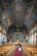Woman vacuuming interior of Church of Santa Maria on Chiloe Island, Chile