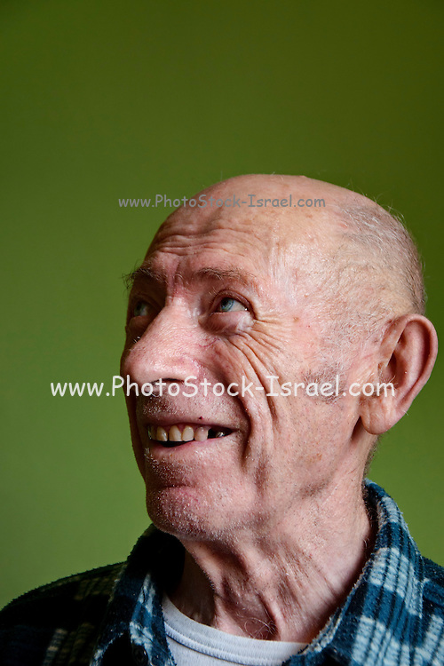 Smiling portrait of a mature man of 75 with green background