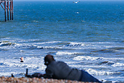 April 6, 2020, London, England, United Kingdom: A swimmer enjoys a dip in Brighton on Monday, April 6, 2020 - as British Prime Minister Boris Johnson was moved to intensive care after his coronavirus symptoms worsened in London. Johnson was admitted to St Thomas' hospital in central London on Sunday after his coronavirus symptoms persisted for 10 days. Having been in the hospital for tests and observation, his doctors advised that he be admitted to intensive care on Monday evening. The new coronavirus causes mild or moderate symptoms for most people, but for some, especially older adults and people with existing health problems, it can cause more severe illness or death. (Credit Image: © Vedat Xhymshiti/ZUMA Wire)