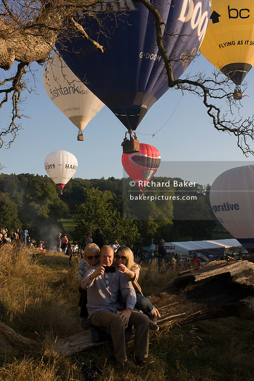 Family takes a selfie during mass lift-off by balloons at Bristols annual fiesta at Ashton Court, UK.