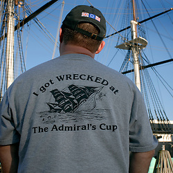BALTIMORE - 4/21/2007 - A man wears a t-shirt advertising The Admiral's Cup, a rewnowned bar in the Fell's Point area of Baltimore.  He stands looking at the USS Constellation, a tall ship docked in the Inner Harbor, and available for tours...Photo by Susana Raab