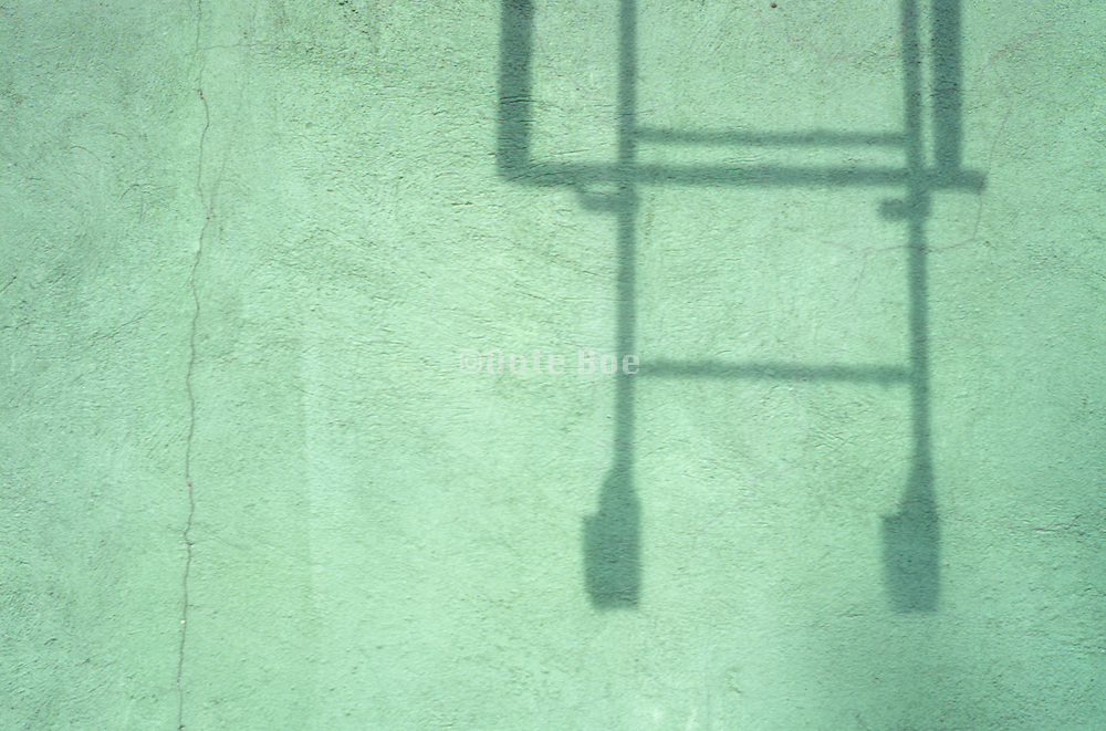 shadow of fire escape ladder on green cracked wall