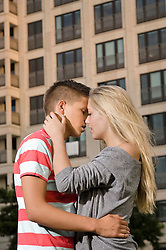 Teenage couple kissing at each other
