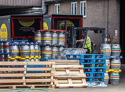 """© Licensed to London News Pictures. 03/07/2020. London, UK. Roll out the Barrels. Workers at Fullers Brewery on the Great West Road, Chiswick load up beer barrels for """"Super Saturday"""" as cafes, restaurants, pubs and hairdressers, prepare for the big opening tomorrow after Prime Minister Boris Johnson gave the go ahead in his statement to the Nation last week. Photo credit: Alex Lentati/LNP"""