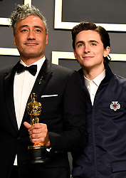 Timothee Chalamet presents Taika Waititi with his Best Adapted Screenplay Oscar for Jojo Rabbit in the press room at the 92nd Academy Awards held at the Dolby Theatre in Hollywood, Los Angeles, USA.