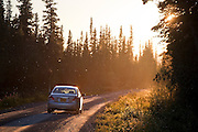 A car drives the McCarthy Road, swarms of flying insects backlit by the setting sun, in Wrangell-St. Elias National Park, Alaska.